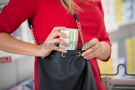 woman stealing capsule packet at supermarket