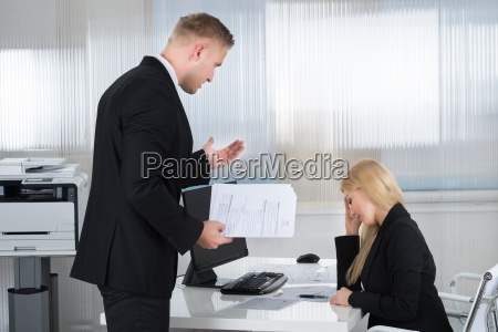businesswoman yelling at employee in office