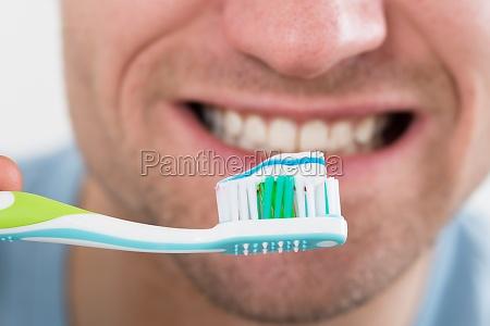 closeup of man brushing teeth
