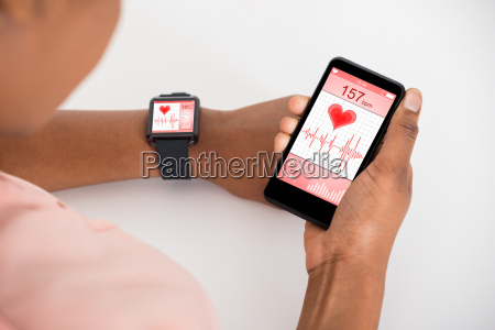 hand with mobile and smartwatch showing