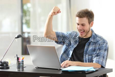 euphoric winner man using a laptop