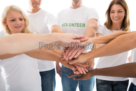 happy multiethnic volunteers stacking hands