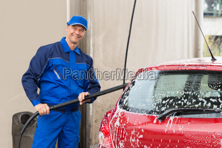 confident male worker washing red car