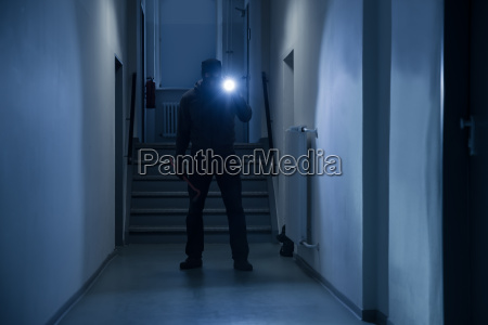 burglar with flashlight and crowbar in