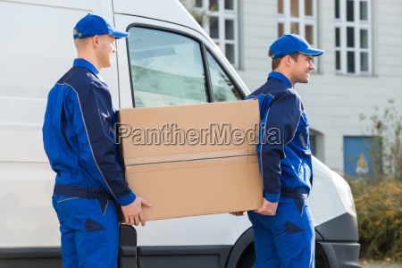 delivery men carrying cardboard box by