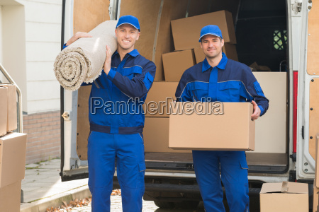 happy delivery men carrying cardboard box