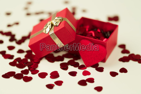red hearts confetti on wooden background