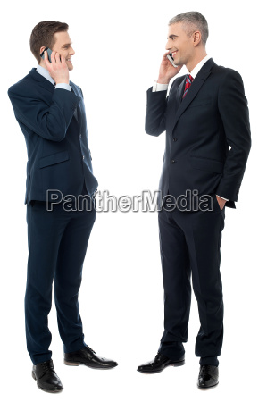 businessmen communicating via cell phone