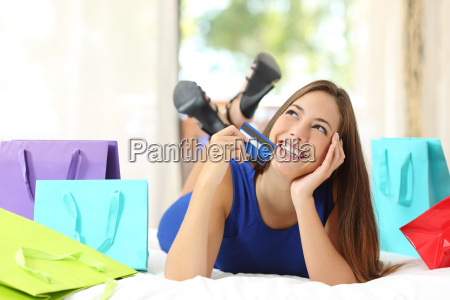 girl holding a credit card thinking