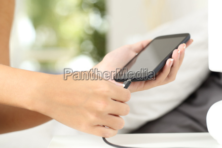 woman, hands, plugging, a, charger, in - 15801199