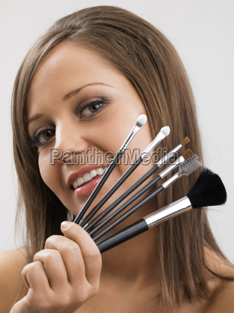 young woman applying make up young
