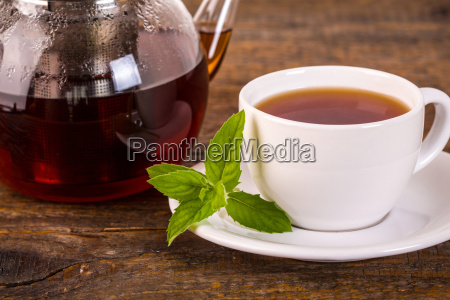 teacup with teapot on wooden table