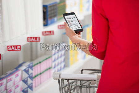 woman checking shopping list on smartphone
