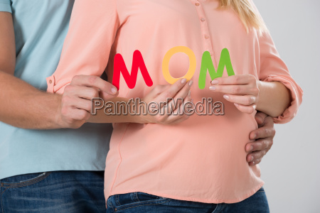 expecting couple holding word mom
