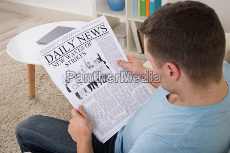 man reading news on newspaper at