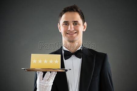 happy waiter holding tray with star