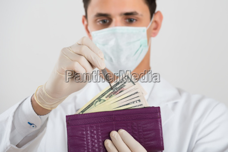 male surgeon removing banknote from wallet