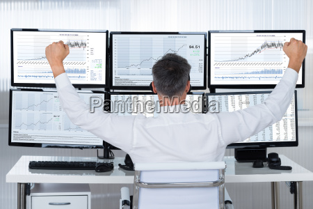 successful trader with arms raised looking