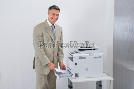 confident businessman using printer in office