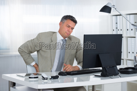 mature businessman suffering from back pain
