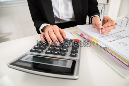 businesswoman doing financial calculation at desk