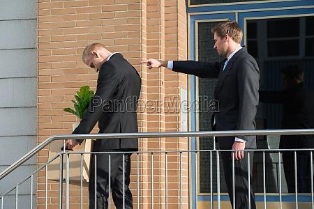 businessman firing employee outside office