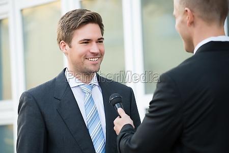 journalist taking interview of happy businessman