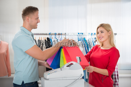 woman taking shopping bags from salesman