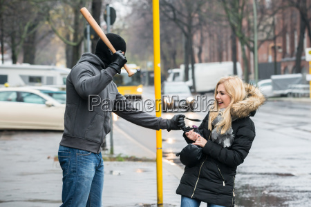 thief hitting woman with bat while