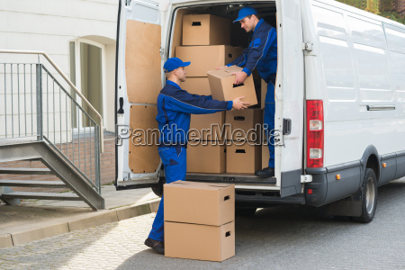 delivery men unloading boxes from truck