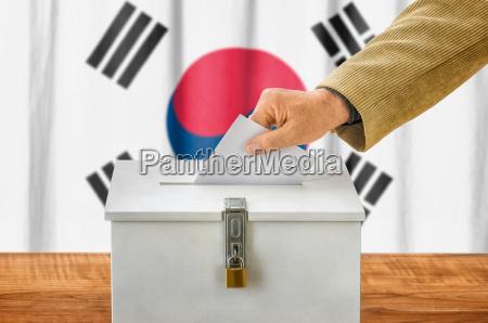 man putting ballot in the ballot