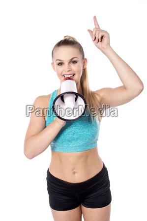 fit lady posing holding megaphone