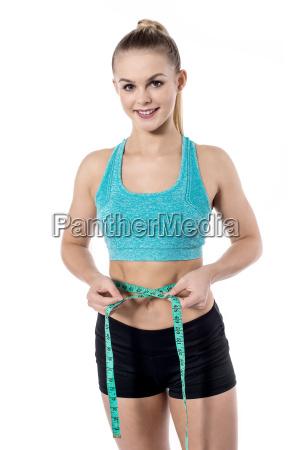 young beautiful woman measuring her waistline