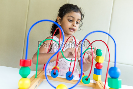 girl play with multi color wood