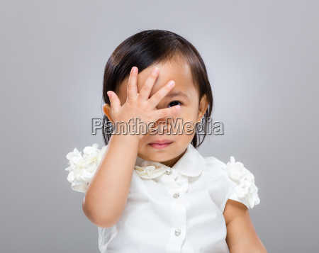 baby girl with hand cover her