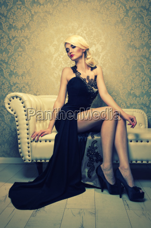 attractive blonde woman sitting on sofa