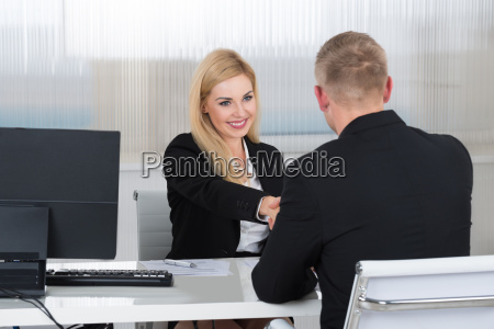 businesswoman shaking hands with male candidate