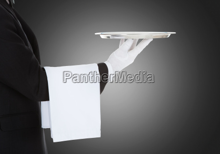 waiter holding empty silver tray over