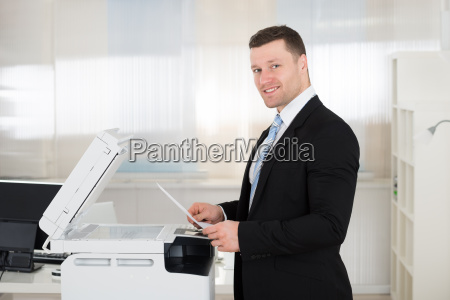 businessman using photocopy machine in office