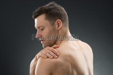 muscular man suffering from shoulder ache