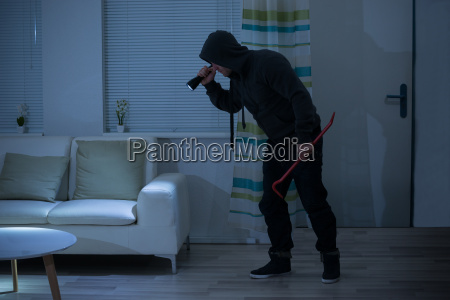 robber with crowbar and flashlight in