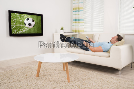 relaxed man watching football match at