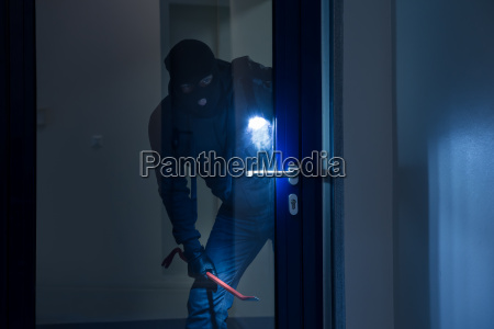 thief with flashlight trying to break