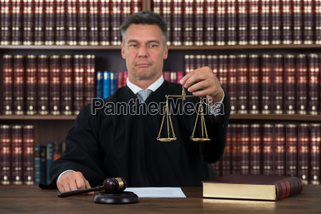judge holding justice scale at table
