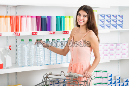 happy woman buying bottle of mineral