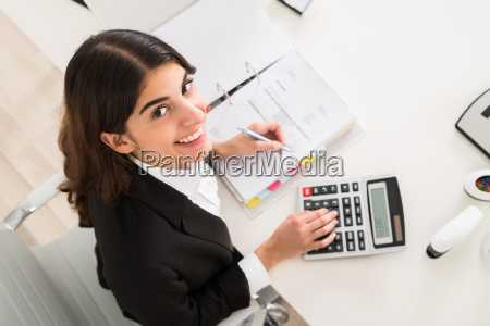 happy businesswoman doing financial calculation at