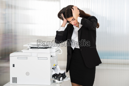 irritated businesswoman looking at paper stuck