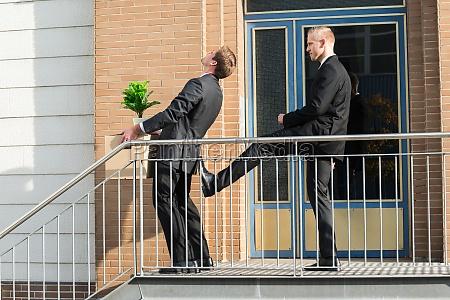 businessman kicking employee with belongings outside