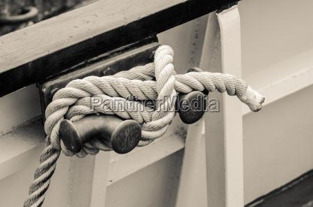 rope tied to bollard sailboat sepia