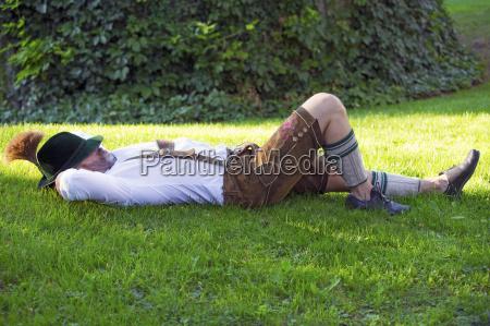 bavarian man sleeping on the grass